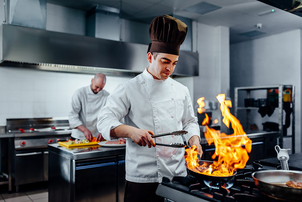 two chefs cooking in a commercial kitchen