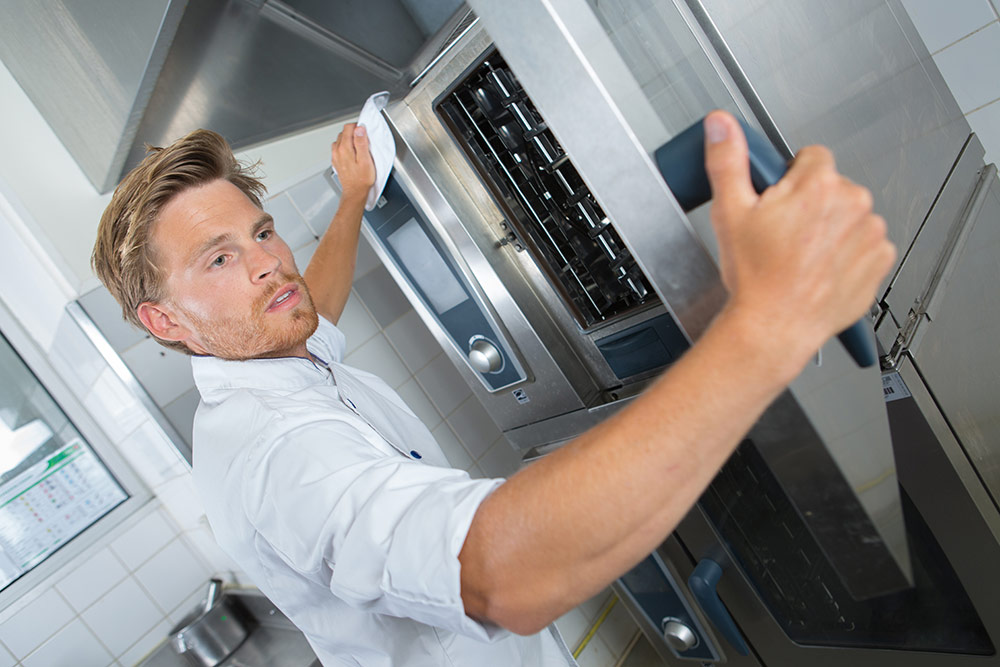 man moving Stainless steel appliances in a commercial kitchen